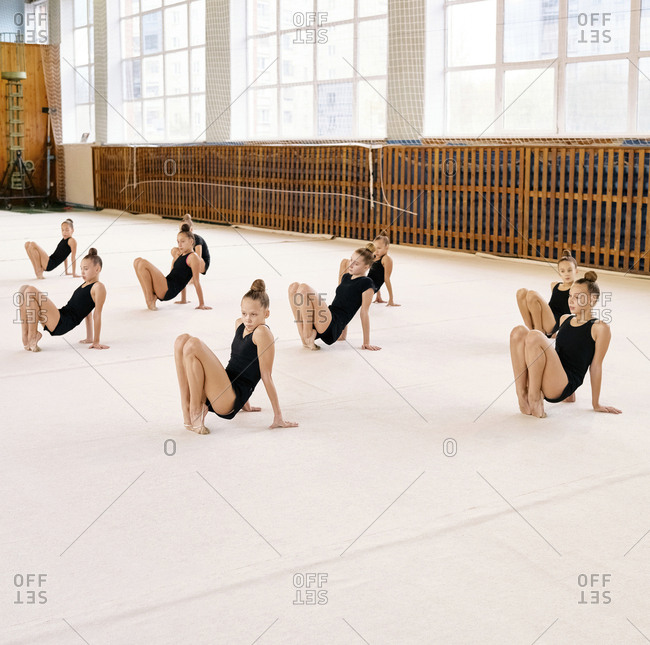 Group of Caucasian girls in training uniform stretching and warming up their feet at school gym while having rhythmic gymnastics class
