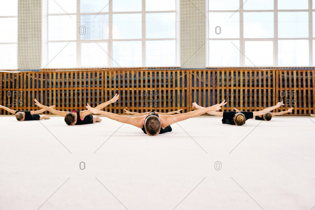 Young girls in black sports clothing lying on the floor with arms outstretched synchronously in a big sport hall