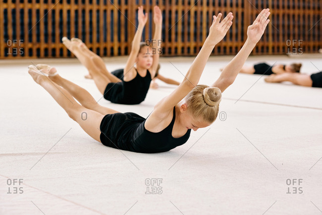 Young blonde girl with gathered hair in bun, black bodysuit exercising and stretching on the floor on gymnastics classes in sport hall