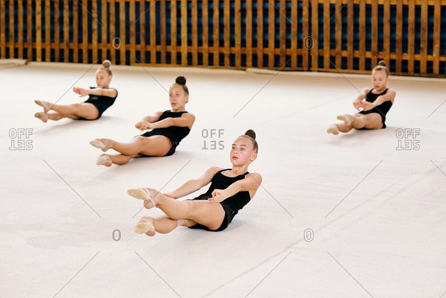 Class of gymnasts in the same sports wear sitting on the floor and showing stretching exercises in sport stadium