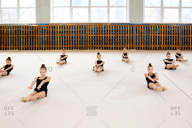 Group of young girls in black sweatsuit sitting on the floor and doing exercises synchronously in a big sport gym at school