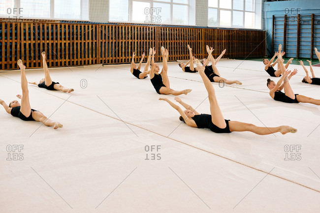 Group of little female rhythmic gymnasts lying on mat and stretching while having training at school gymnasium