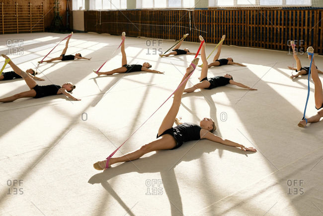 Group of young gymnasts are doing stretching exercises with colorful resistance bands while lying on exercise mat in sport school stadium