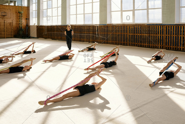 Group of teenage Caucasian female athletes exercising on the floor with rubber bands, they doing stretching exercises in sport gym