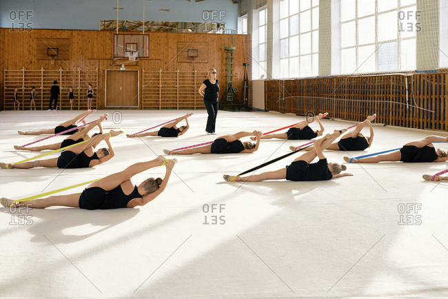 Athletic little girls wearing black uniform stretching with rubber bands while lying on the floor with coach training them in sport hall