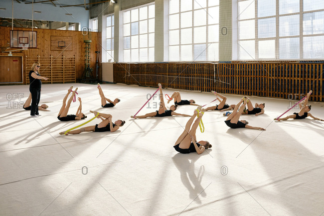 Young gymnasts wearing black uniform training with rubber bands with their instructor during gymnastics class at school