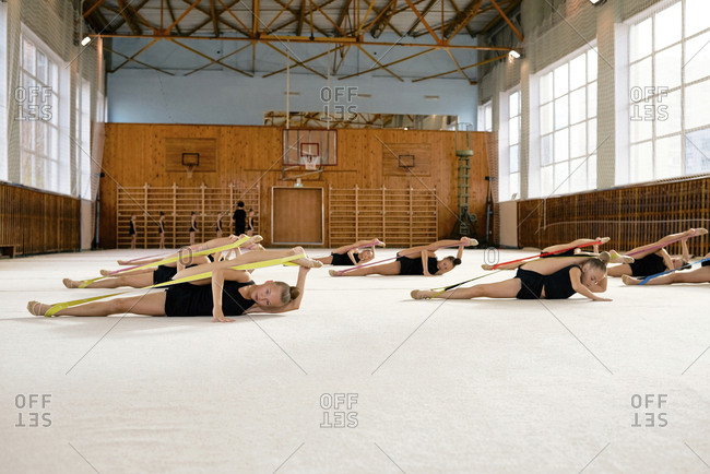 Plastic young gymnasts doing warming up exercises with resistance bands during gymnastics class at school