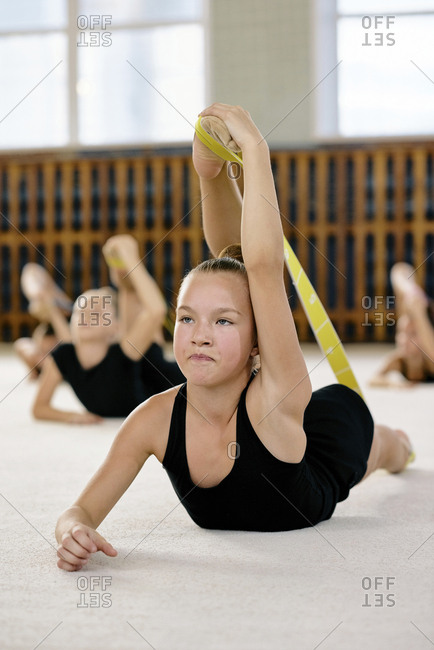 Portrait of young beautiful girl in black sports wear lying on exercise mat and stretching using rubber band with other girls in the background