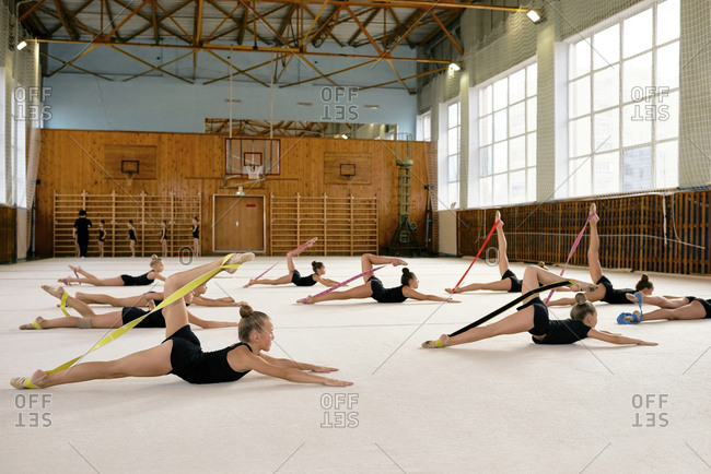 Group of little girls in training uniform stretching and warming up with rubber bands in sports hall at school