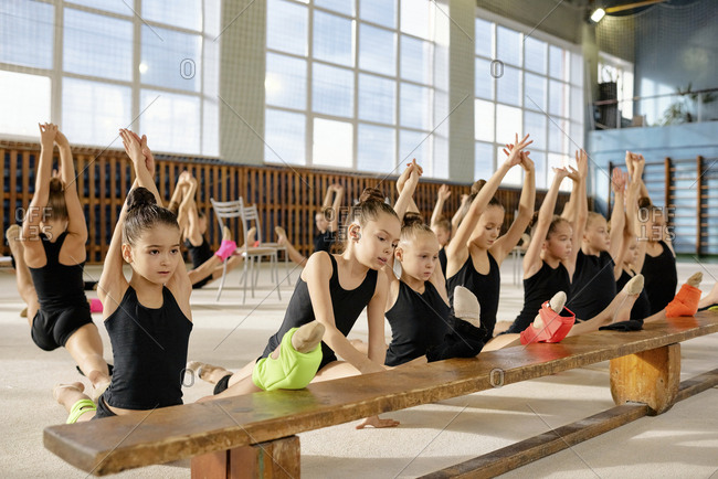 Group of little gymnasts doing splits near the bench with their hands raised and keeping the balance during training