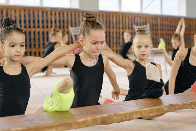 Little girl in black sportswear doing splits through tears with other gymnasts at gymnastics classes in gym