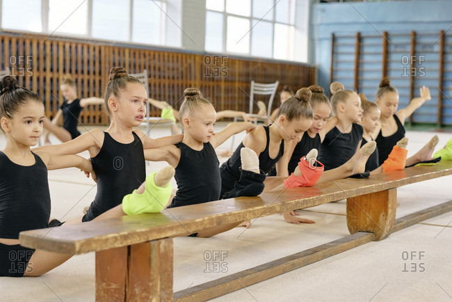 Little gymnasts in black uniform warming up before training doing splits on the bench in sport school stadium
