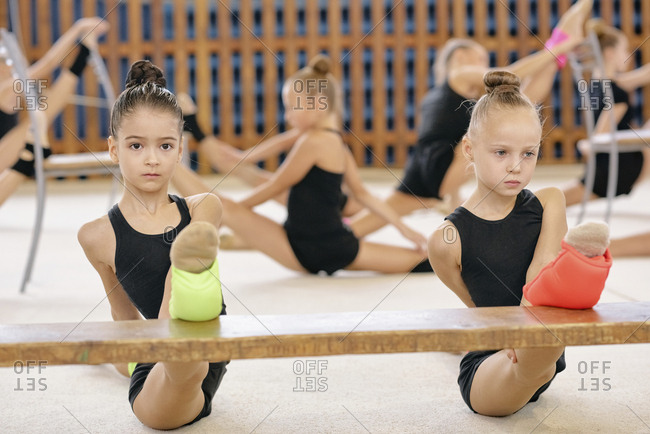 Portrait of two young gymnasts in black uniform doing splits on bench during gymnastics classes with other gymnasts in the background