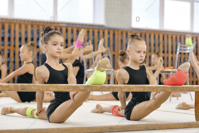 Concentrated beautiful gymnasts stretching legs on bench during training in sport gym at school