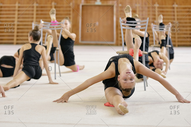 Portrait of young professional gymnast sitting on splits during training with other gymnasts in the background in sport hall