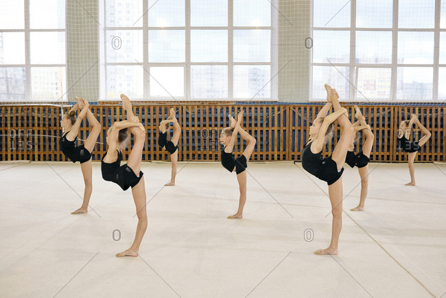 Group of girls in black sweatsuit doing vertical leg-split exercise during gymnastic classes in the gym