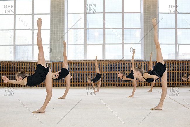 Group of little Caucasian female athletes standing in pose doing vertical splits while having rhythmic gymnastics class at school gymnasium