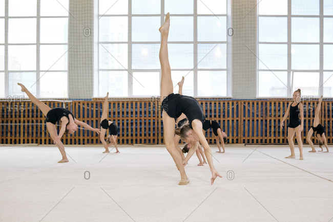 Group of girls warming up before classes, they standing and stretching their legs in sport school gym