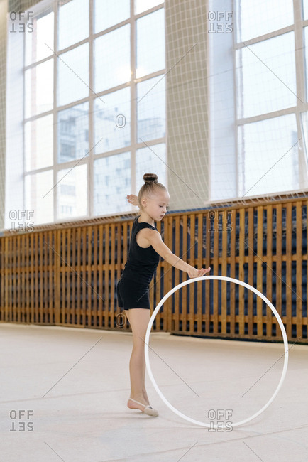 Portrait of little girl in black sports clothing exercising with hula hoop, she dancing solo during gymnastics classes at school