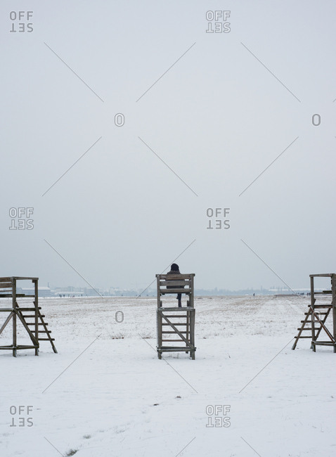 Person sitting in a wooden lookout on a snowy field