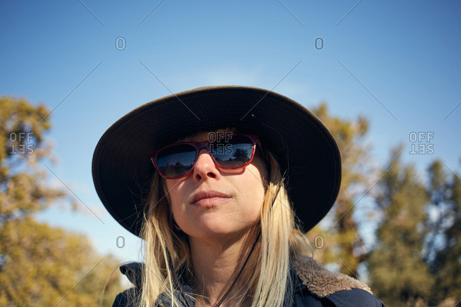 Portrait of a woman wearing a hat and sunglasses outside in nature