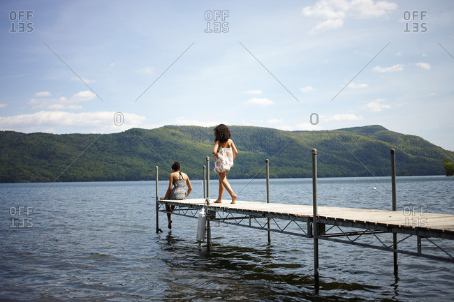 Young women walking and sitting on a dock along a mountain lake