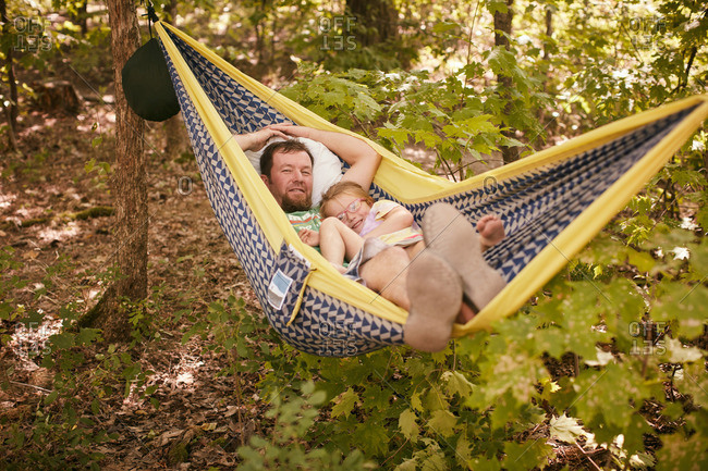 Father and daughter relaxing together in hammock in the forest