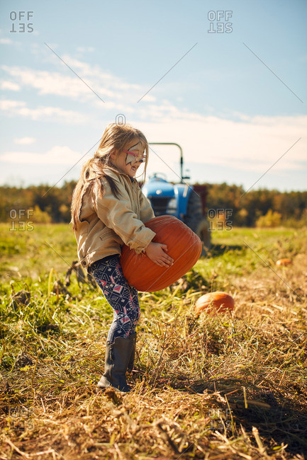 Girl with a painted face lifting a heavy pumpkin in a field
