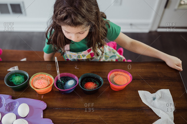 Girl watching her easter eggs changing color in dye