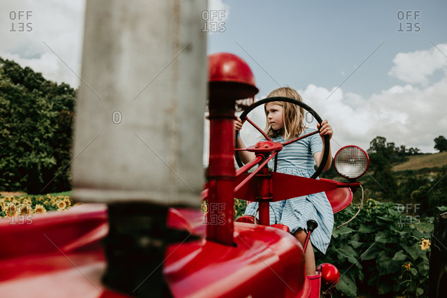 Little girl sitting on a tractor