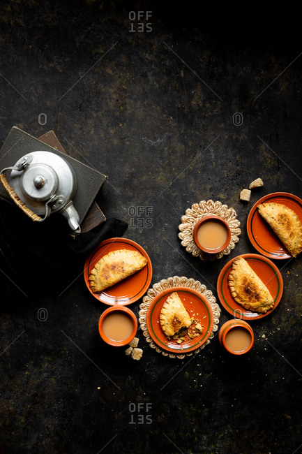 Overhead view of baked savory hand pies and tea kettle