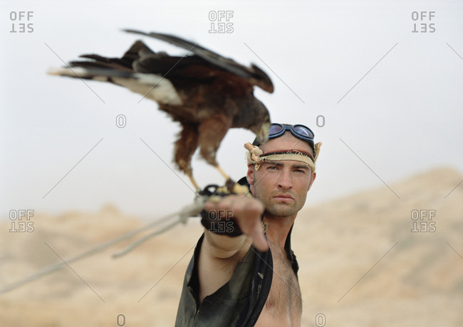 Portrait of a young man standing with a bird of prey perched on his wrist.