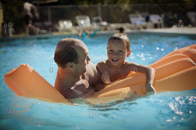 father and son playing in pool on raft