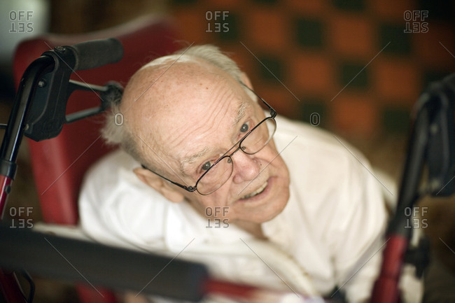 Side view of an old man on a wheel chair.