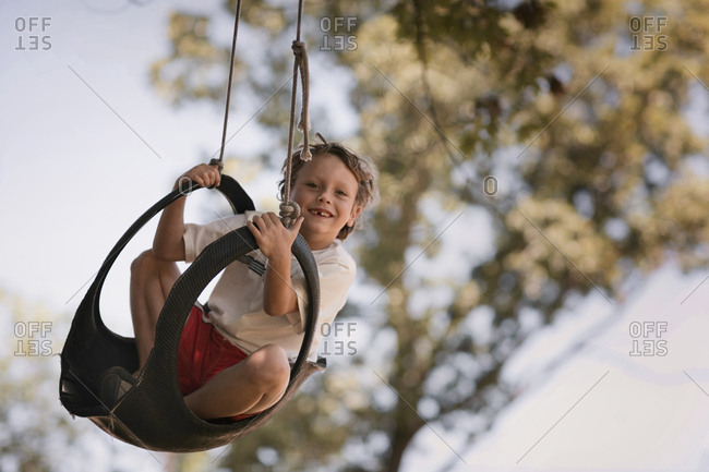 child swings in tire swing