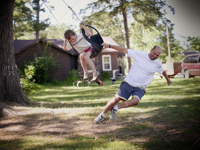 father pulls chld in tire swing