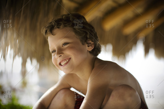 Portrait of a topless boy sitting under the thatched canopy.