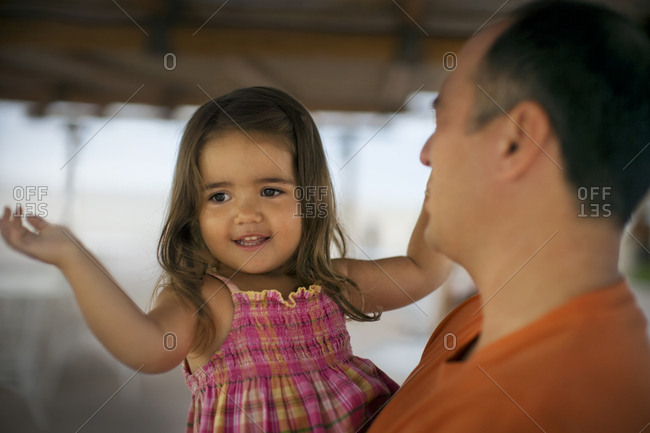 Portrait of a father holding his daughter in the arms.