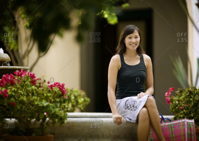 A young woman smiles while sitting amidst flowers