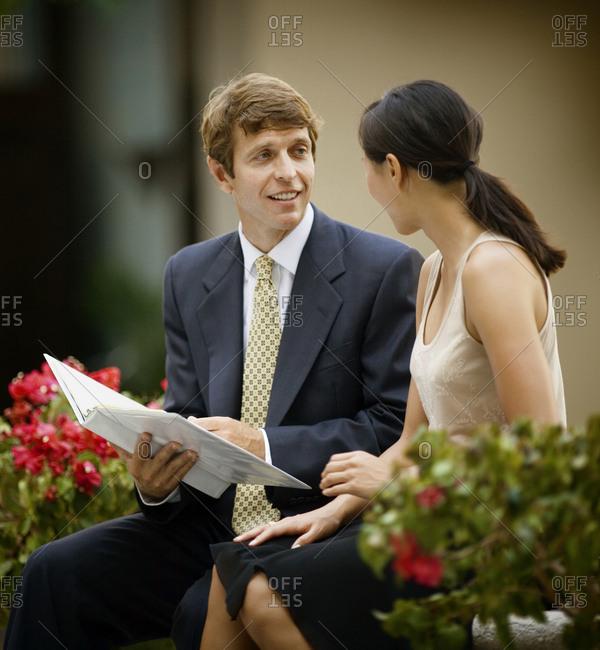 Business professionals discuss official matters amidst plants.