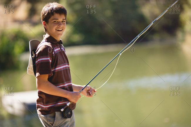 Teenage boy having fun fishing on a lake.