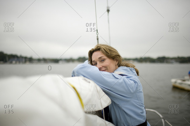 Portrait of a mature adult woman resting on a lowered sail of a boat.