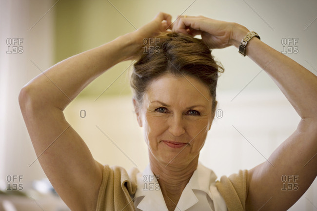 Portrait of a mature adult woman putting her hair up.