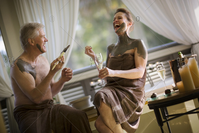 Mature couple laughing while covering each other in mud inside their bathroom.