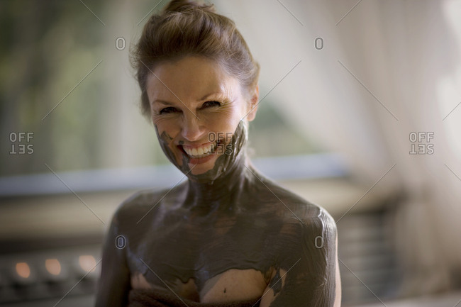 Portrait of a mid-adult woman having mud mask applied to her body.