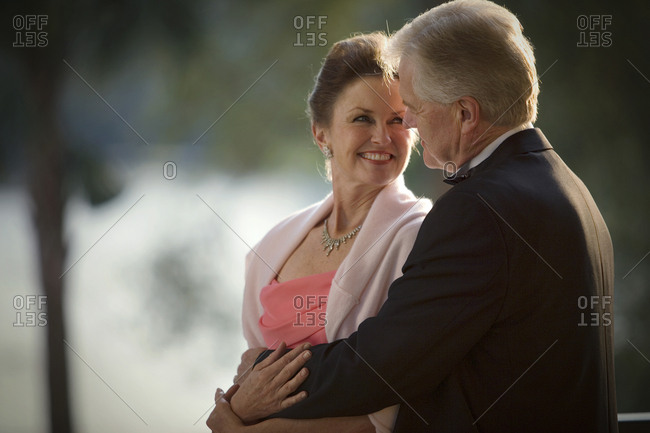Mature adult couple dressed formally showing affection.