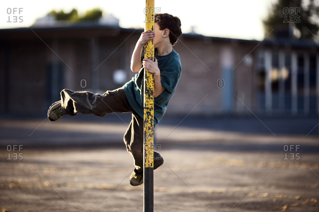 View of a little boy trying to swing around a metallic pole.