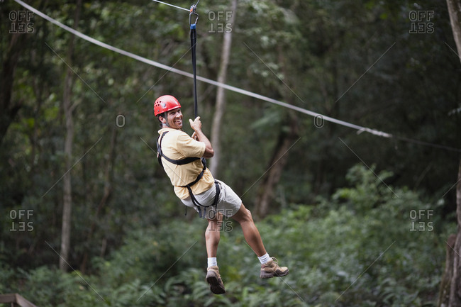 Man swinging through trees on rope with harness