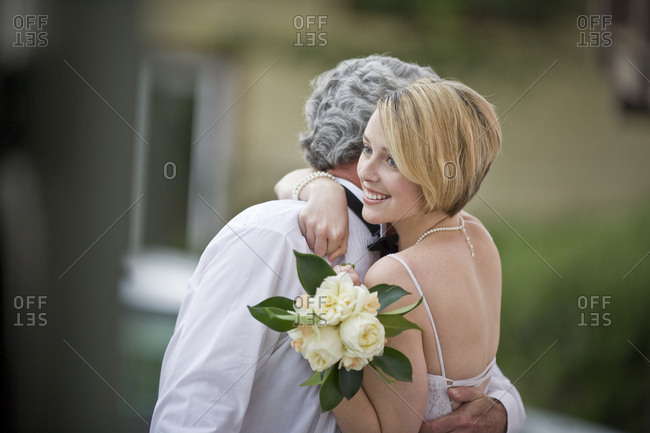 Smiling bride hugging the groom while holding a bouquet of roses.