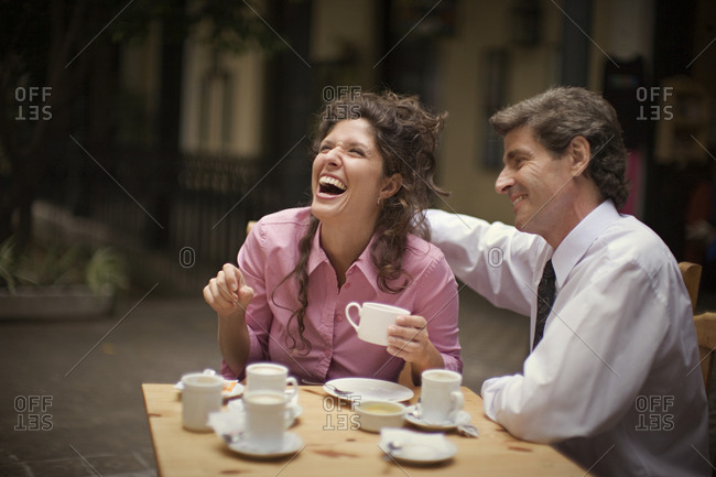 View of a cheerful couple enjoying a cup of coffee.